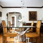 glass dining table with gorgeous silver post white wall white ceiling beautiful glass hanging lamps yellow patterned dining chairs with silver frame elegant oval mirror silver candleholder