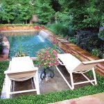 gorgeous inground swimming pool with interesting fountain and cozy twin lounge chairs with eco-friendly area for modern house concept