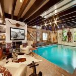 gorgoeus indoor swimming pool with magnifcent wooden ceiling and amazing cozy rustic sofa with wall mount shelve furniture
