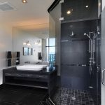 gorgeous black bathroom with amazing vanity and shower space with interesting large transparent glass mirror in black ceramic flooring