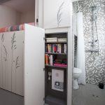 gray mozaic tiles wall gray ceramic tiles floor white patterned small doors hidden bookshelves mounted steeled shower white toilet gray painted ceiling gray simple pendant lamp
