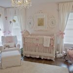 hardwood flooring luxurious chandelier white blinds white curtains with pink ribbon white easy chair white crib with soft pink ribbon decoration white wall white ceiling wahite side table white arch lamp