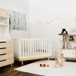 hardwood flooring white rug simple white wooden crib white wall white and light brown wood open shelf white and light brown cabinet railing wall lamp flower picture