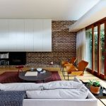 interesting brick wall and elegant living space design with cozy couch and unique round coffee table also wonderful sliding doors with wall mout bookshelves