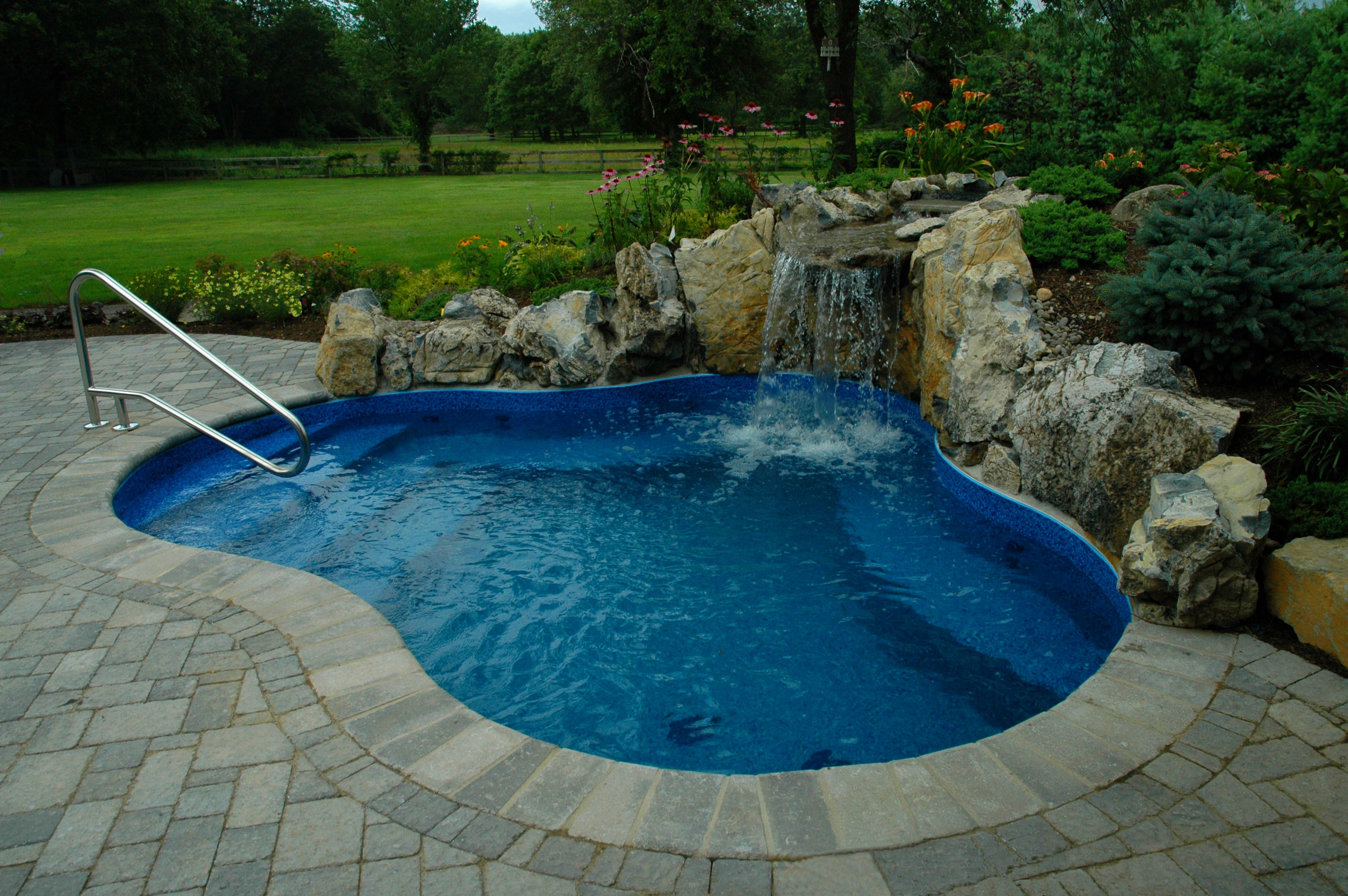 interesting small swimming pool with gorgeous mini waterfall also hardstone  paving overlooking green grass land