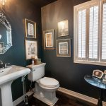 interesting black bathroom with elegant white singk and bidet also interesting classic style mirror with golden accent in hardwooden flooring