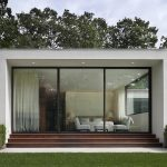 intereting cube home architecure with forest backdrop also magnificent large glass window with cozy white loft sofa and interesting white low profile bed