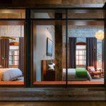 large glass window wooden floor brick wall rustic wooden pilar great pendant lamp white bedspread wooden armchair industrial bedroom design comfortable bedroom
