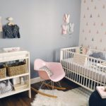 light blue painted wall white painted wall with colorful triangle picture white cimple crib pink cute rocking chair white chanhing station white cozy rug wooden floor cute baby nursery room