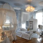 light blue with cloud painted wall wooden varnished floor beautiful white crib with curtain white small bed white storages beautiful chandelier white small rocking chair girly baby nursery room