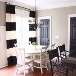 light gray painted wall black painted interior doors black and white striped drapery white painted ceiling white painted dining set black dining chairs cute black chandelier wooden varnished floor
