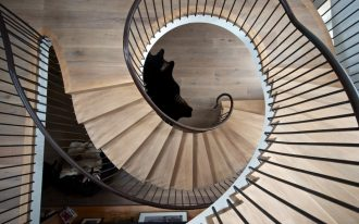 light wooden floor light wooden treads steel balustrade upright leathered handrails black furry floor rug whirling staircase design huge modern staircase