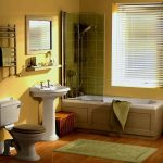 light yellow painted wall white pedestal sink wooden varnished floor white toilet green plush rug wooden framed mirror rattan basket large wondow warm atmosphere bathroom