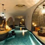magnificent indoor swimming pool with cozy lounge chairs and unque half round ceiling with extravagant bar area in the middle also interesting pendant lamp