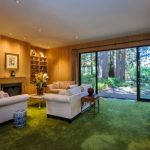 magnificent sliding glass door overlooking nature view feat cosy white leather soda and elegant wooden wall panel with gorgeous green carpeting ideas