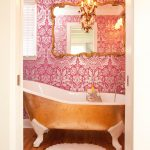pink vintage wallpaper wooden varnished tile flooring clow foot bathtub gold vintage framed mirror gold metal chandelier white fringed mat white framed window