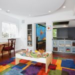 ravishing basement playroom with assorted color rug also small white table with elegant storage and cozy wooden armchair in laminate flooring