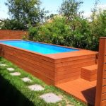 rectangular in deck swimming poll wooden deck floor stony footpath green grass lush plantations small swimming pool idea