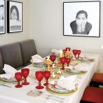 red dining shairs grey dining long chairs white wall red glasses white table cloth gold candelabra gold red and white plate set white cloth potrait framed wall decorations