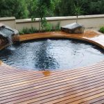round in deck swimming pool stony water dripper wooden deck floor green and lush environment beautiful scenic view small swimming pool idea