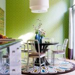 soft pink tile flooring green wall with unique pattern white hanging lamp dark brown round rug with exceptional pattern round dark wood dining table white chairs with wood seating blue video