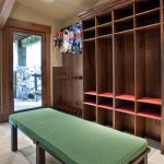 stoe flooring dark wood open cabinet blue blue and red hanging skatebords white wall white ceiling downligh glass door with wood frame wall wood hook plae green chair
