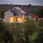 stony outdoor wall luminious holiday house twilight sky lush green vegetation beautiful scenery cozy holiday house design