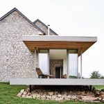 stony outdoor wall stony indoor wall tall glassed sliding door wooden ceiling brown leathered chair stone foundation refreshing green grass cozy holiday house design