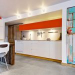 unqie basement apartment with sleek kitchen idea also old fashioned blue door with ravishing hardwooden table for dining set also cute orange and white accent in concrete floor idea
