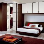 white and frameless bedroom cabinets elegant black square table thick red carpet circular bed dark wood cupboard white ceramic tile colorful pillow cases white bedroom wall red blanket square standing la