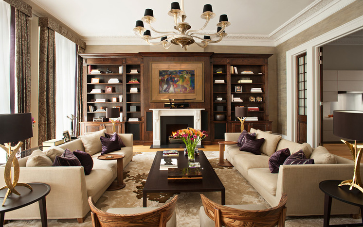 white ceiling beige rextured wall beige sofas dark purple pillows dark brown coffee table round black side table white and black fireplace wood cabinet gold chandelier glass vase black gold table lamp