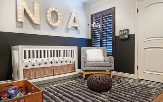 white ceiling white and black wall hardwood flooring white crib dark brown wooden window white door cute white lighting baby's name white fur cushion grey wavy rug black and white blocked armchair