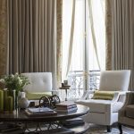 white curtain with floral broder white blind white armchairs gold cushions dark wood round table white framed window beautiful grey and white rug green candles gold hanging lamp