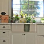 white kitchen cabinets white sink white painted wooden wall gray marble countertop green leafy plants in pots simple steeled pendant lamp healthier and greener kitchen