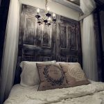 white mosquito net wood canopy whiite bed sheet white lace bed cover white pillows black and gold chandelier cream wall brown pillows door painted wall as headboard