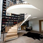 white painted ceiling light wooden floor english oak treads black furry rug black upholstered armchair black high bookcase steeld balustrade upright whirling staircase design