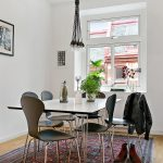 white painted wall black dining chairs patterned rug simple pendant lamp white dining table black framed pictures simple white dining room bright dining area