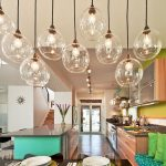 White Painted Wall Light Wooden Kitchen Cabinets Black Marble Kitchen Countertop Bright Green Painted Wall Glass Covered Pendant Lamps Green Cushions Bright Kitchen
