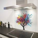 white painted wall white kitchen cabinet black marble kitchen countertop white painted ceiling steeled smoke sucker colorful artsy tree image in glass splashback glass splashback design