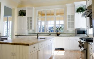 white wooden kirchen cabinets bright marble countertop light wooden varnished floor white ceramic tiled backsplash white painted wooden framed window bright kitchen