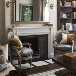 whte and gold sconces grey armchair with gold frame white fireplace white wall dark brown wood open bookshelf grey rug dark wood coffee table white sofa white and gold pillows grey and gold framed mirror