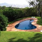 wonderful heart shaped small swimming pool with elegant orage stone paving and amazing white lounge chair eith open grass graden overlooking the nature view