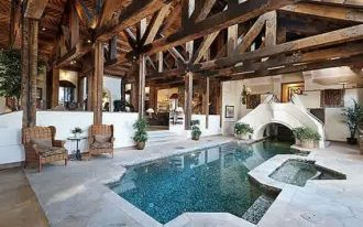 wonderful indoor swimmming pool with antique wooden roofing and magnificent two armchair in flastone deck