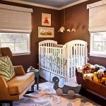 wonderful nursery room with amazing brown wall accent and elegant white crib with soft brown sofa with many dolls design in beautful blue rug idea