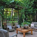 wood armchairs wood table stripped cushion flower patterned cushion beautiful wood pergola grey cushion brown vase gravel ground open patio