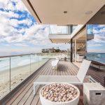 wooden terrace floor glass separator white outdoor chair glassed window glassed sliding door beautfiul blue sky contemporary villa design in Malibu