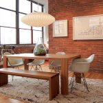Wooden Varnished Dining Table Wooden Varnished Long Stool White Armchairs Wooden Varnished Floor Brick Wall  Ufo Shaped Pendant Lamp White Bicycle Square Patterned Dining Rug