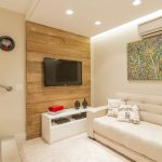 wooden wall white counter white sofa colorful abstract wall white painted ceiling urban wall mounted plate white cozy rug urban patterned cushion Vila Mariana in Brazil by Cristiane Bergesch