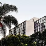 The hotel design building with many floors surrounded by green trees modern hotel design of The Line Hotel in Koreatown Los Angeles