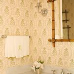 Artichoke Patterned Green And Light Yellow Wallpaper White Towel Bamboo Framed Mirror Green Sconce With Metal Frame Metallic Vase White Vanity White Undermount Sink Metal Towel Hanger